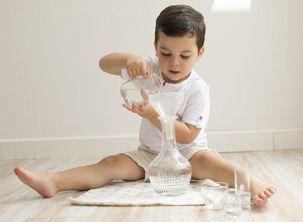 El niño de 18 meses le encanta juguar con el agua.