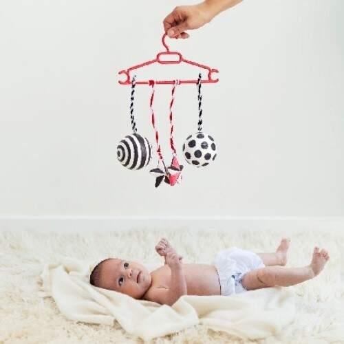 Jugando con el bebe recien nacido, con juguetes en balanco y negro